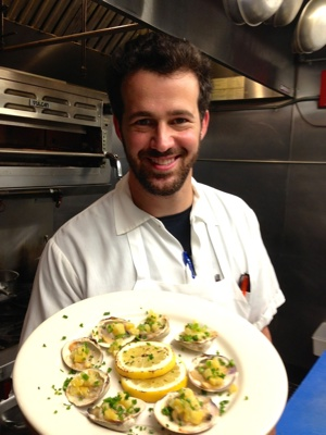 Chef Aaron Oster Holding the Port Hunter's Hickory Grilled Clams with Jalapenos and Preserved Lemon