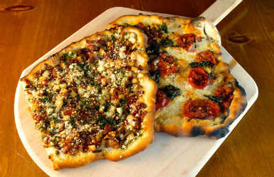 Grilled pizza on wooden pizza peel