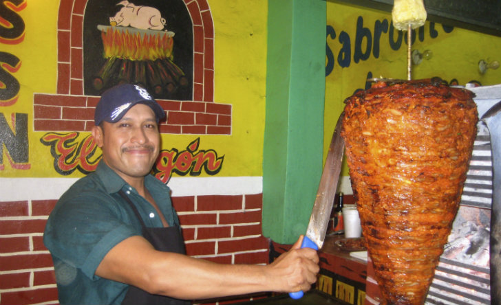 Carving the pork for tacos al pastor