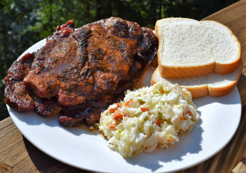 Pork steaks on plate with bread and slaw
